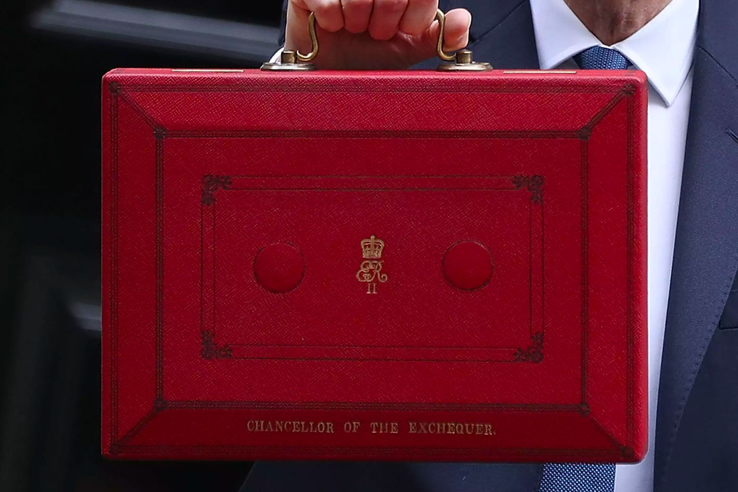 Chancellor holding up red briefcase