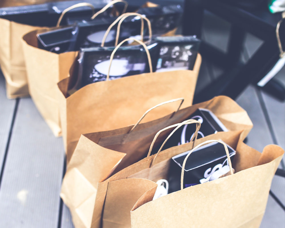 multiple brown paper bags with purchases inside