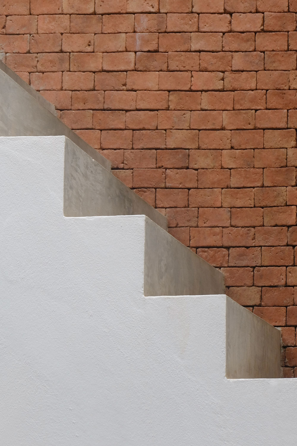 side view of concrete stairs with a brick wall