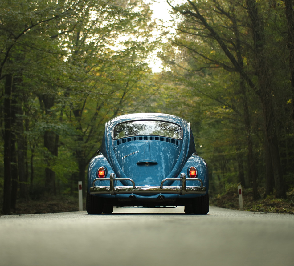 rear view of a blue VW driving down a country land