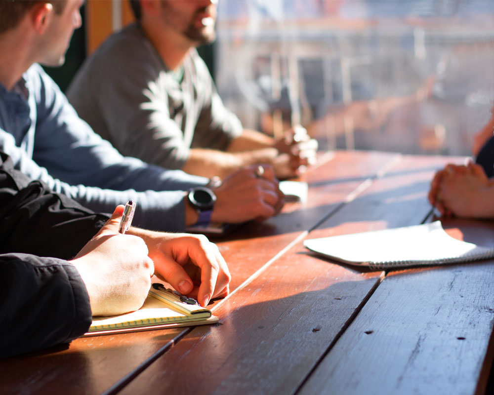 men sat around a table having a business meeting