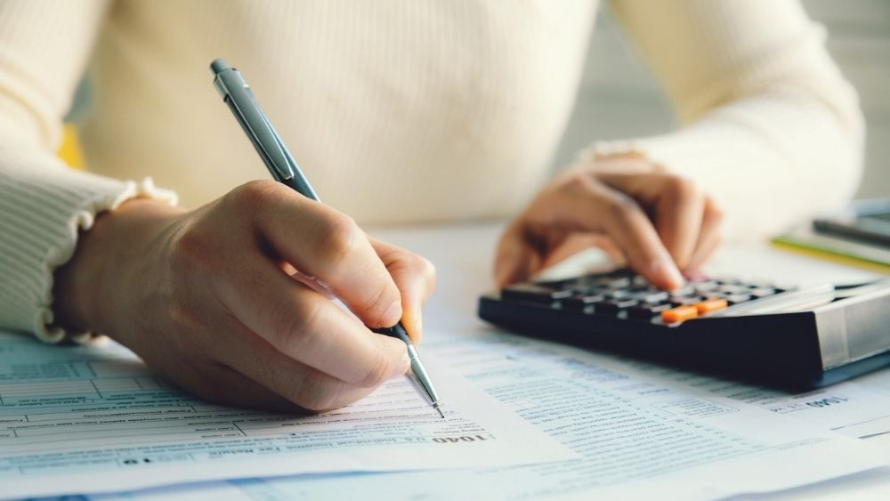 womans hand on calculator depicting how to include the SEISS grant on a tax return