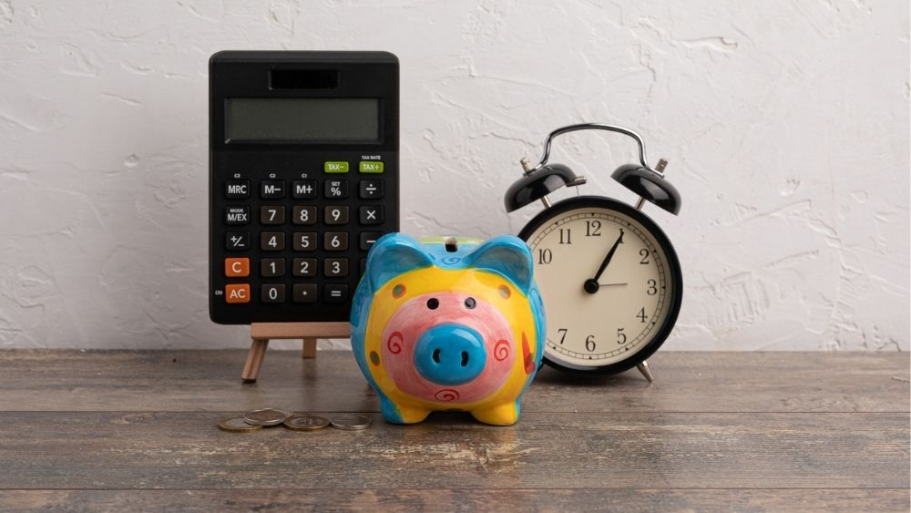 A calculator, piggy bank and clock on a desk indicating simplified tax reporting